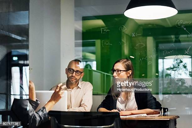 Business meeting behind a glass wall