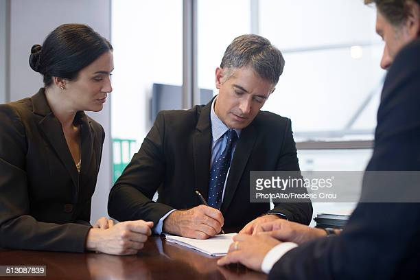 Business meeting, businessman signing document while associates observe