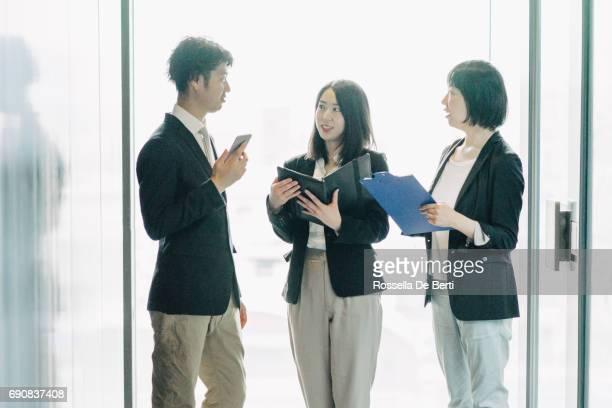 営業会議、新しいプロジェクトについて議論する同僚