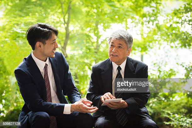 business meeting in a park - green suit stock pictures, royalty-free photos & images