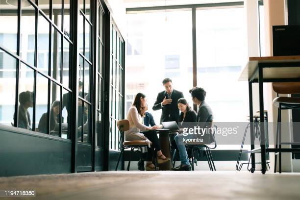 business meeting in co-working space - kyonntra stock pictures, royalty-free photos & images