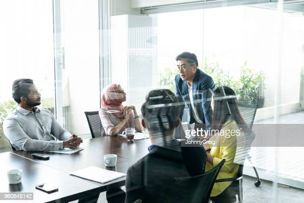 business meeting in modern office view through glass - business meeting stock pictures, royalty-free photos & images