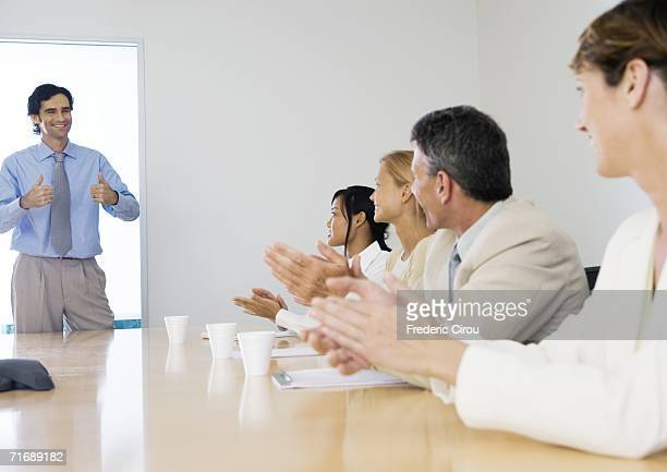 business meeting, man standing with thumbs up while colleagues clap - pep talk stock pictures, royalty-free photos & images