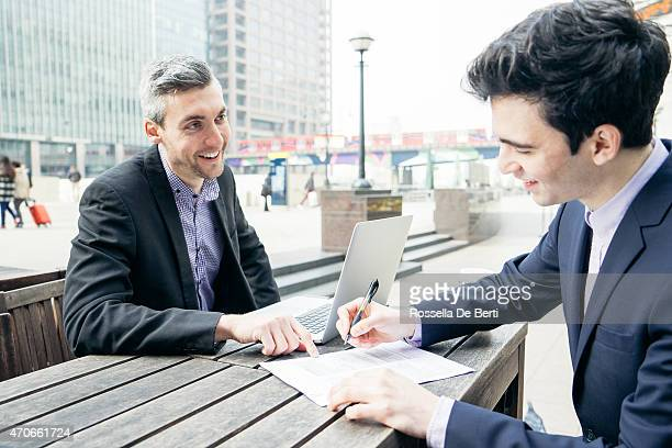 Business Meeting Outdoors, Businessmen Discussing A Contract