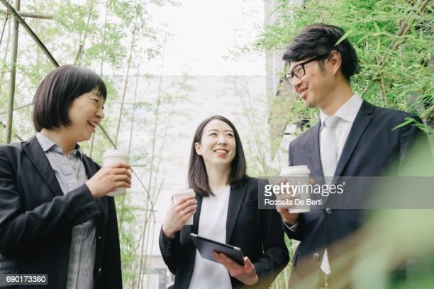 営業会議屋外で、新しいプロジェクトを議論する同僚