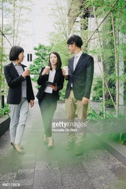 Réunion à l'extérieur, leurs collègues discuter d'un nouveau projet d'affaires