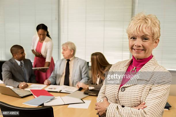Business meeting. Senior adult businesswoman and her team. Board room.