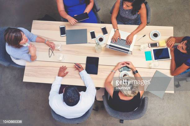 business meeting shot from above. - conference table stock pictures, royalty-free photos & images
