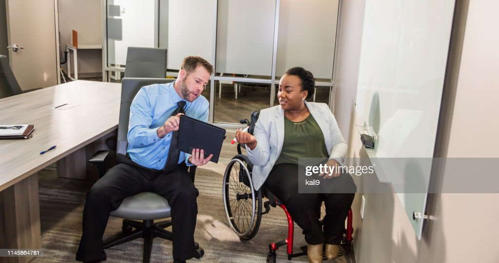 Business meeting, woman in wheelchair at whiteboard : Stock Photo