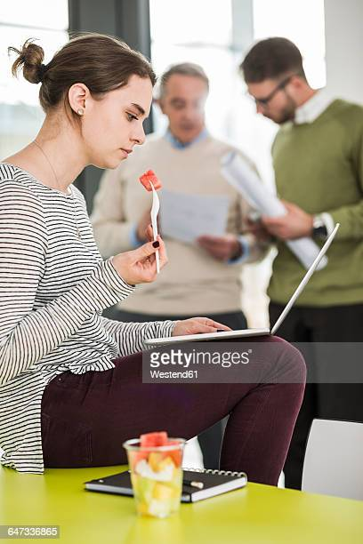 Business meeting, young woman eating water melon