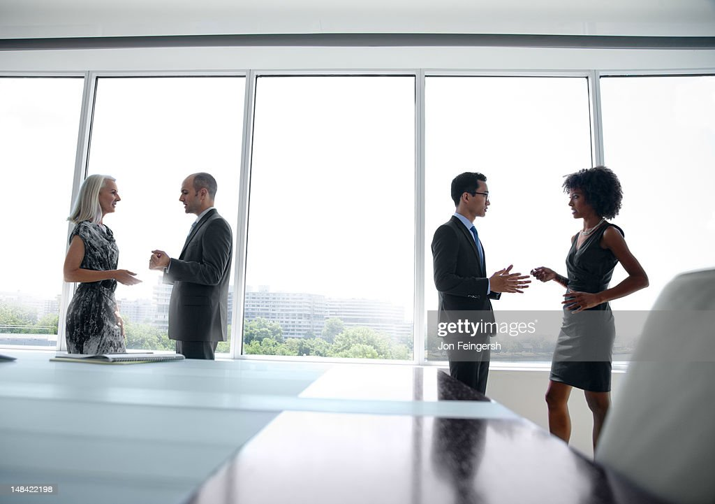 Business men and woman talking by window : Stock Photo