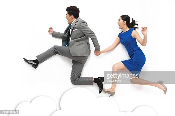 Business men and women holding hands run
