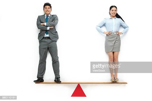 Business men and women on the seesaw