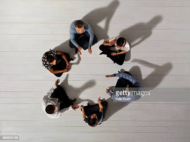 Business men and women sitting in circle