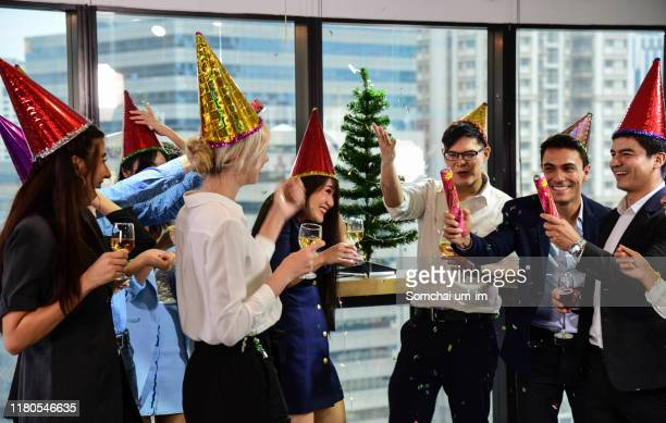 business men and women with glasses of champagne celebrating christmas and new year - party stock pictures, royalty-free photos & images