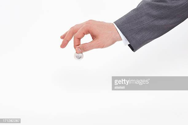 business men hand throwing coin to the piggy bank