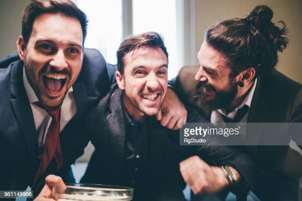 business-männer umarmten und unterstützen ihre lieblings-fußball-teams in aufregung - sportbegriff stock-fotos und bilder