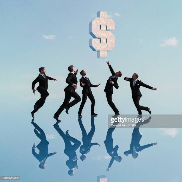 business men leaping up to reach for floating dollar sign - greedy smith stock pictures, royalty-free photos & images