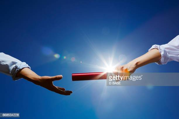 business men passing the red baton. - relay baton stock photos and pictures