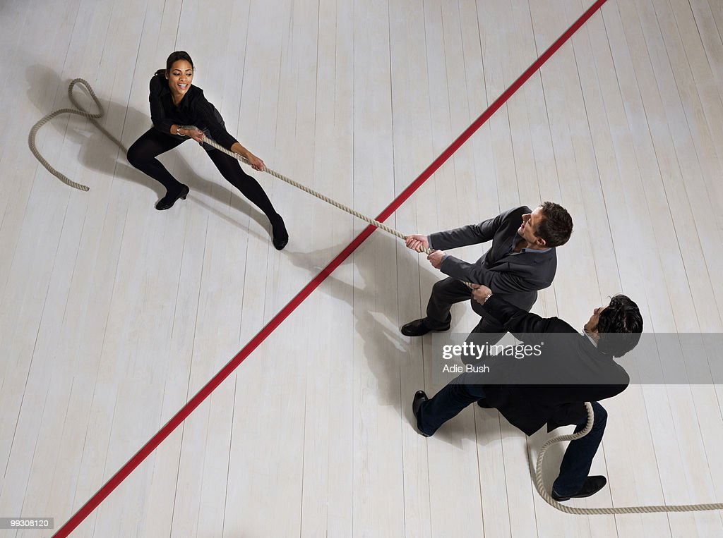 Business men pulling woman with rope : Stock Photo