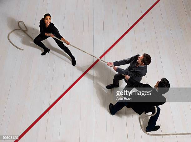 business men pulling woman with rope - gender identity stock pictures, royalty-free photos & images