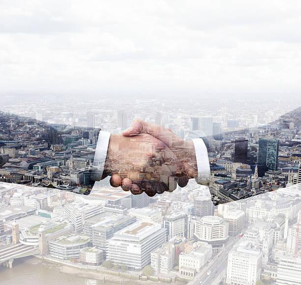 Business Men Shaking Hands Above City View. Wall Art