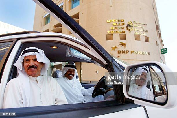 Business men sit in front of the United Gulf Bank Tower November 252002 in Manama Bahrain With war in Iraq on the horizon the Middle East is...