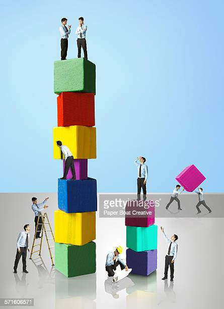 business Men standing on colored wooden blocks