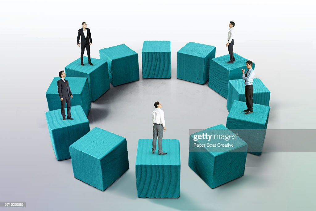 Business men standing on wooden blocks in a circle : ストックフォト