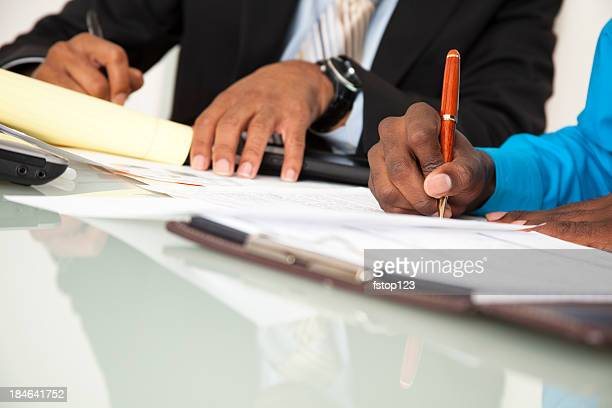 Business men taking notes at office meeting. African descent. Paperwork.