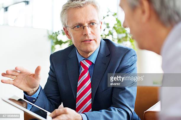 business men talking over a tablet - white hair stock pictures, royalty-free photos & images