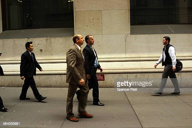 Business men walk in the financial district on April 11 2014 in New York City In early morning trading the Dow was down over 70 points following a...
