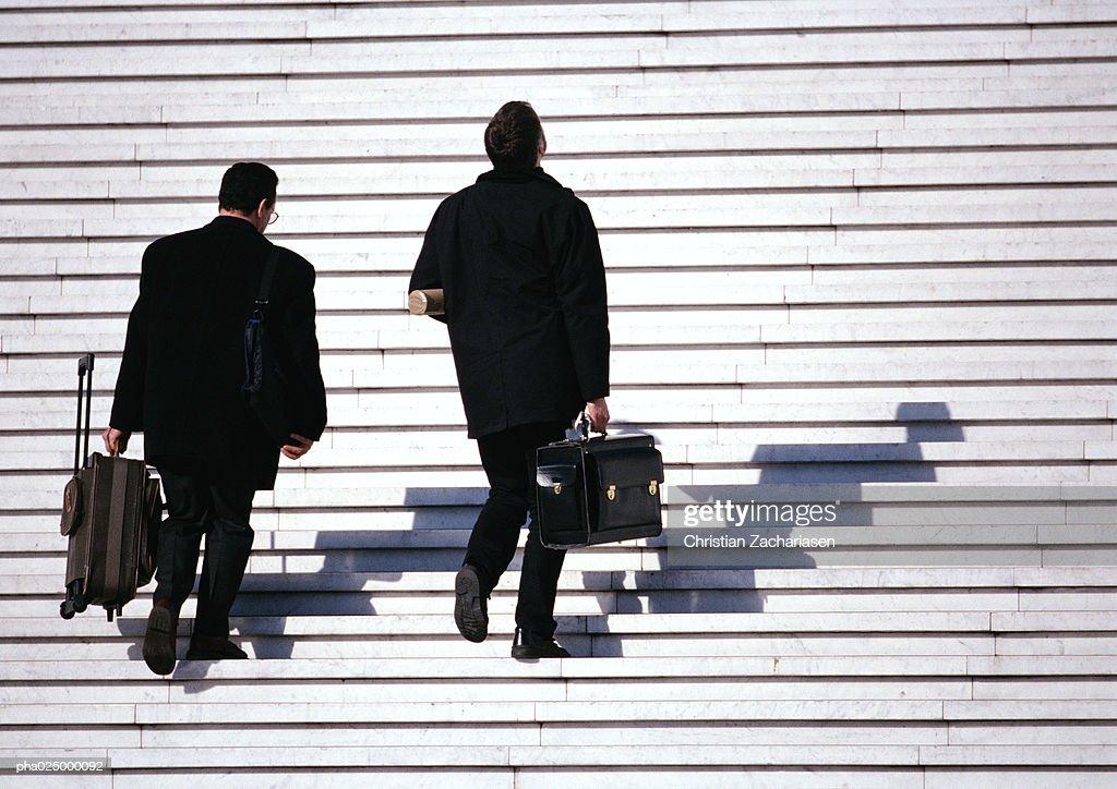 Business men walking up steps : Stockfoto