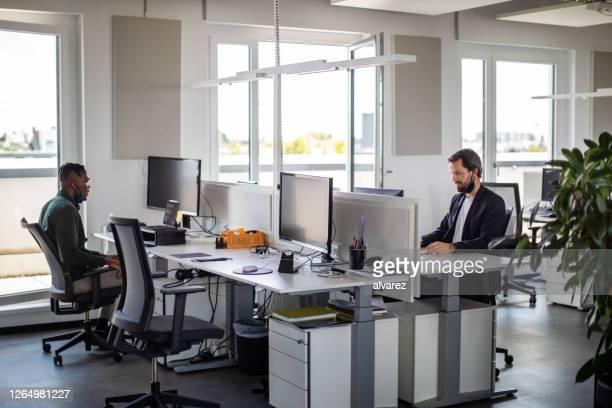bedrijfsmensen die in bureau tijdens pandemie werken - office stockfoto's en -beelden