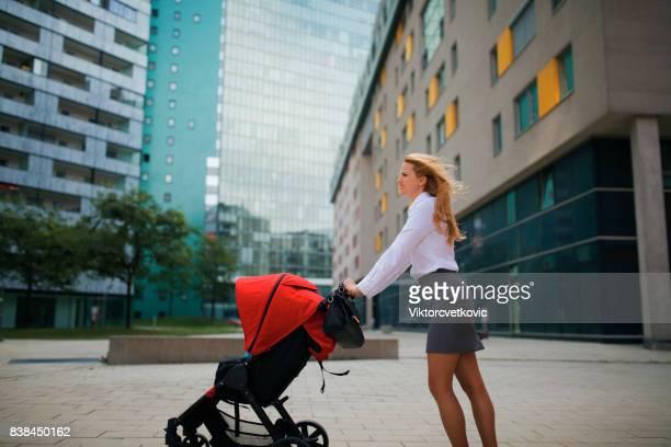 Geschäft Mutter schob einen Kinderwagen auf der Straße