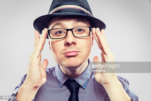 Business Nerd with hat on adjusting his glasses