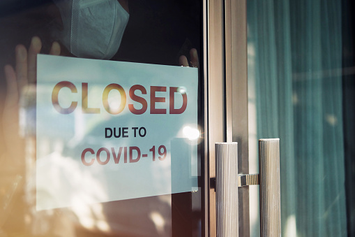 Business office or store shop is closed/bankrupt business due to the effect of novel Coronavirus (COVID-19) pandemic. Unidentified person wearing mask hanging closed sign in background on front door. 1216449625