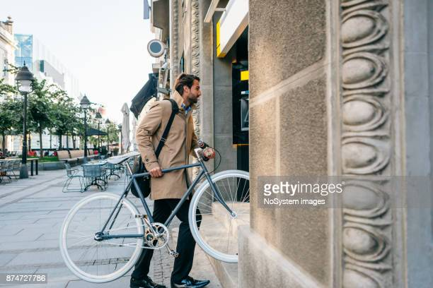 Business on the Go. Businessman lifting bicycle up steps into building