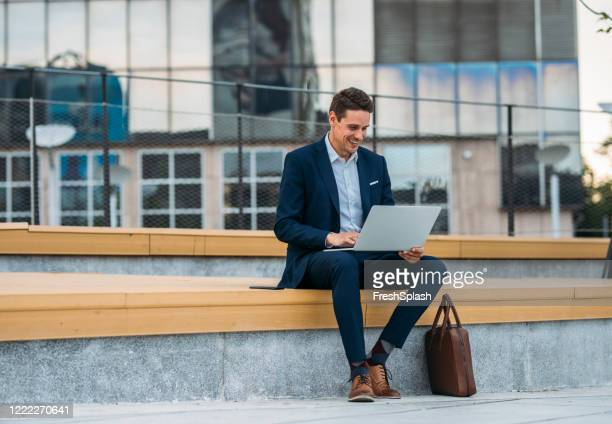 business on the go: businessman working on his laptop on the street - bench stock pictures, royalty-free photos & images