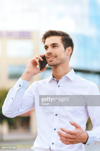 bedrijf in beweging - zakenman financiële district gebruikend smartphone voor communicatie - alleen jonge mannen stockfoto's en -beelden