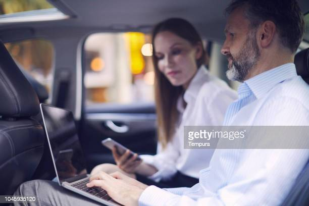business on the move, riding a car and working in the backseat. - car pooling stock photos and pictures