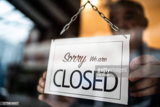 business ower holding closed sign on storefront door - closing stock pictures, royalty-free photos & images