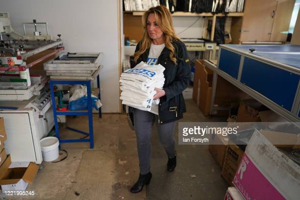Business owner Alison Hylton carries a finished batch as she produces NHS branded t-shirts on April 30, 2020 in Hartlepool, England. Mrs Hylton's...