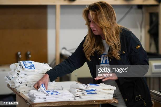 Business owner Alison Hylton stacks a finished batch of NHS branded t-shirts on April 30, 2020 in Hartlepool, England. Mrs Hylton's normal business...