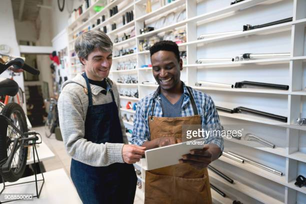 Business owner and salesman looking at comments of their store on a tablet looking very happy