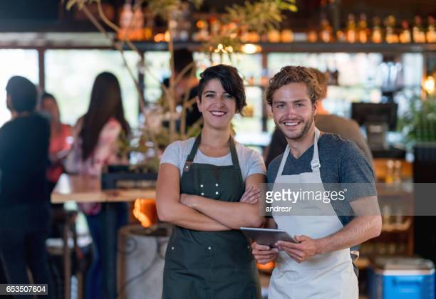 Business owner and waiter working at a bar using a tablet computer