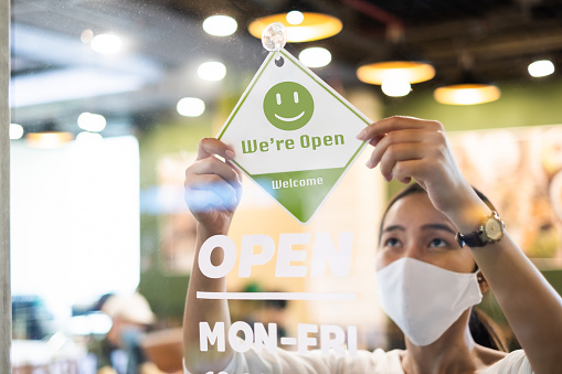 Business owner Asian woman wear protective face mask ppe hanging open sign at her restaurant / café, open again after lock down due to outbreak of coronavirus covid-19 1223180112