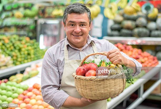 Business owner at a food market holding a basket