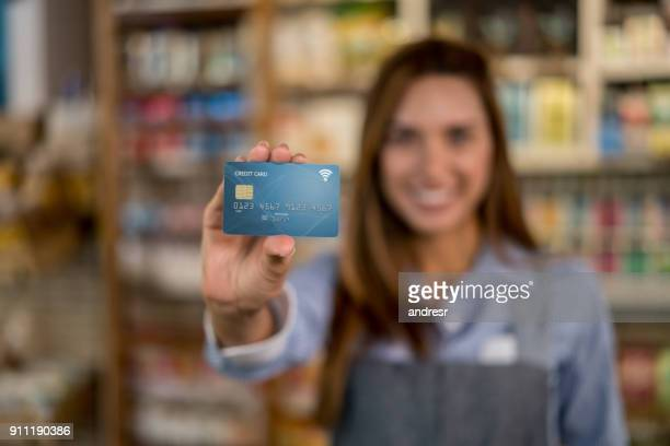 Business owner at a food market holding a credit card