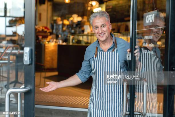 business owner at the door of a cafe welcoming customers - greeting foto e immagini stock